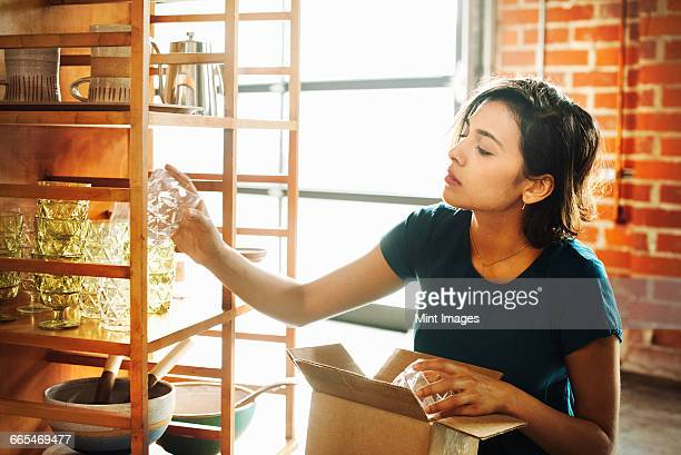 Young woman in a shop, placing a drinking glass on a shelf.