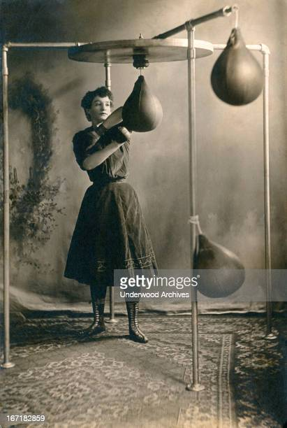 A young woman in a skirt working out with boxing gloves and a punching bag 1890