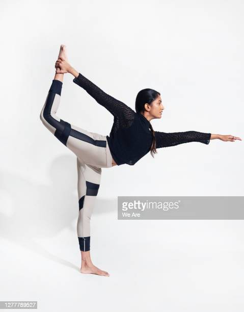 young woman in a standing yoga pose - yoga stock pictures, royalty-free photos & images