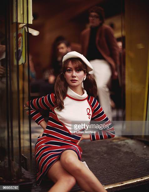 A young woman in a striped mini dress and a white beret poses in a doorway circa 1968