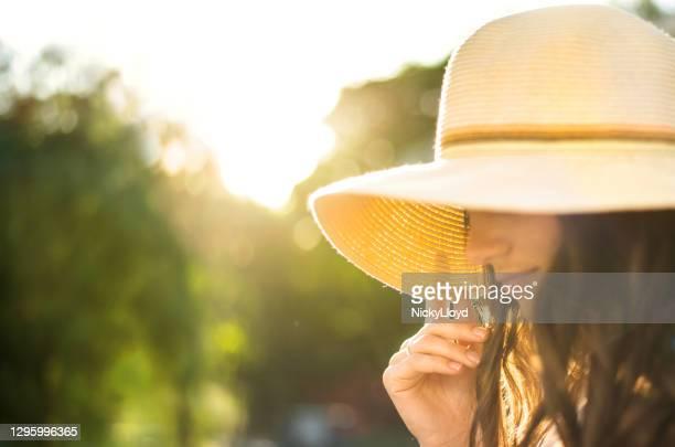 晴れた午後に外に立っている太陽の帽子をかぶった若い女性 - つば広 ストックフォトと画像
