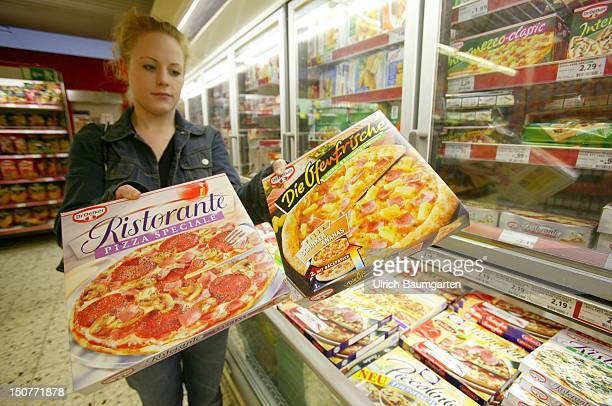 Young woman in a supermarket at a freezing compartment holding two pizzas of the producer DR Oetker