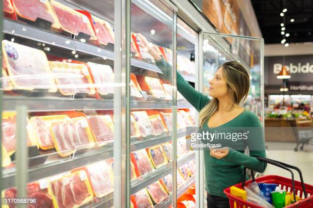 young woman in a supermarket buying meat - meat stock pictures, royalty-free photos & images
