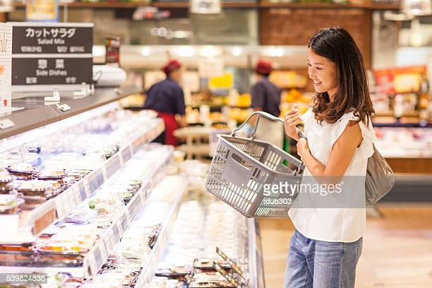 young woman in a supermarket looking in the deli section - delicatessen stock pictures, royalty-free photos & images