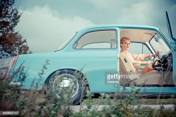 Mujer joven en un coche de época