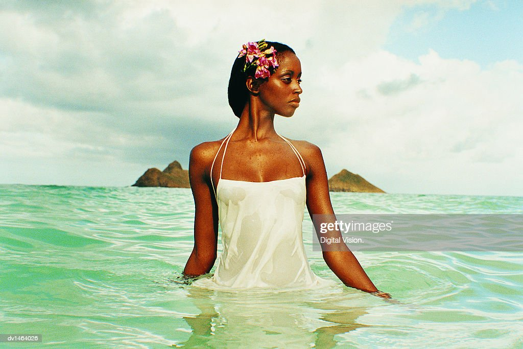 Young Woman in a Wet Negligee Walks Waist Deep in the Sea : Stock Photo