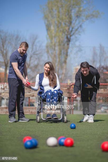 young woman in a wheelchair and his friends are playing boccia - paraplegic woman stock photos and pictures