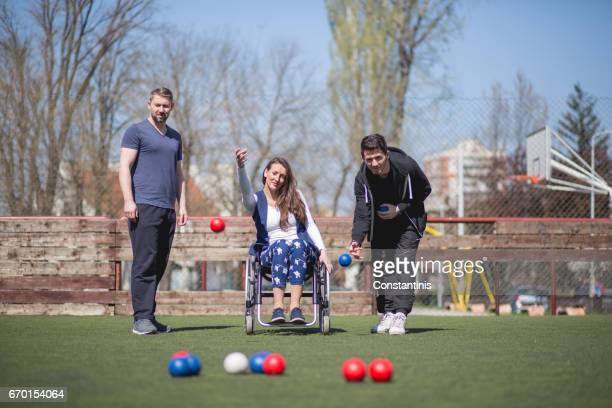 young woman in a wheelchair and his friends are playing boccia - assistive technology stock photos and pictures