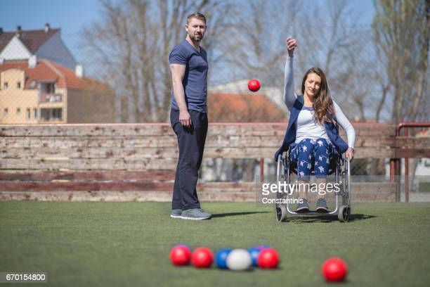 young woman in a wheelchair and his friends are playing boccia