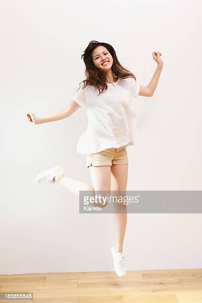 Young woman in a white shirt jumping
