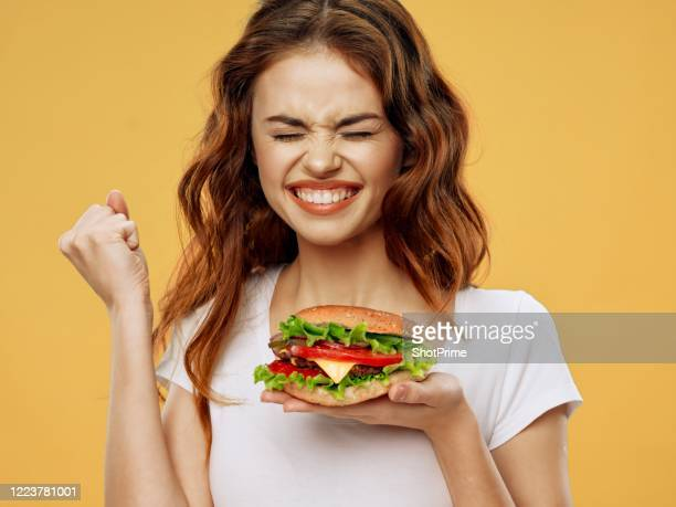 a young woman in a white t-shirt holds a big burger in one hand and shows the yes gesture with the other hand. - burger stock pictures, royalty-free photos & images