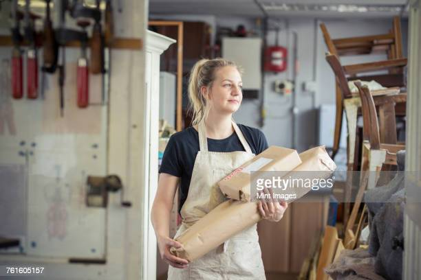 A young woman in a workshop, holding two packages wrapped in brown packaging paper, ready for despatch.