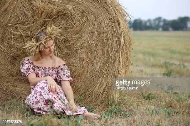 young woman in a wreath of wheat against haystack - une seule jeune femme photos et images de collection