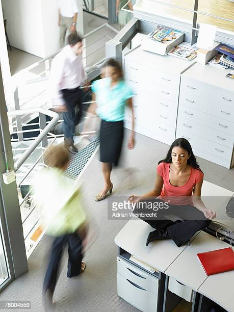 Young woman in a yoga position sitting on her work desk