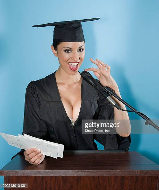 Young woman in academic regalia touching microphone, smiling, portrait