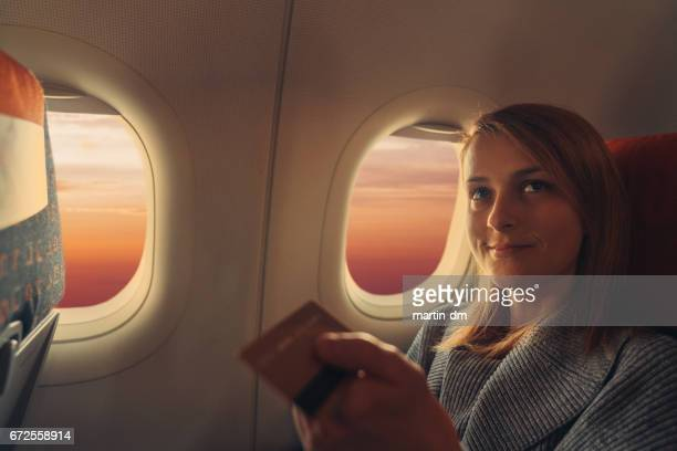 Young woman in airplane paying with credit card