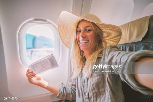 young woman in airplane takes mobile phone selfie portrait during flight - airplane ticket stock pictures, royalty-free photos & images