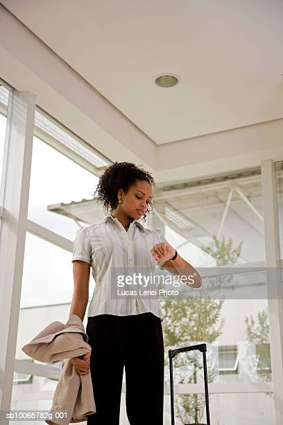 Young woman in airport lobby, checking watch