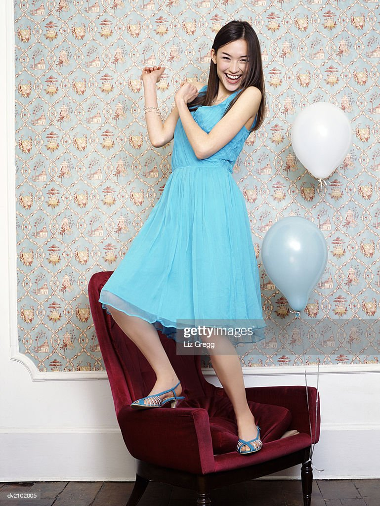 Young Woman in an Evening Gown Dances on Top of an Armchair : Stock Photo