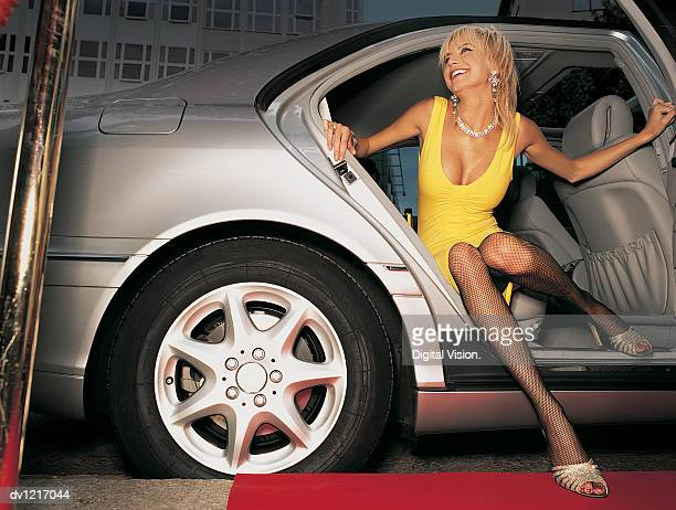 young woman in an evening gown getting out of the back seat of a car onto a red carpet - celebrity cleavage stock photos and pictures