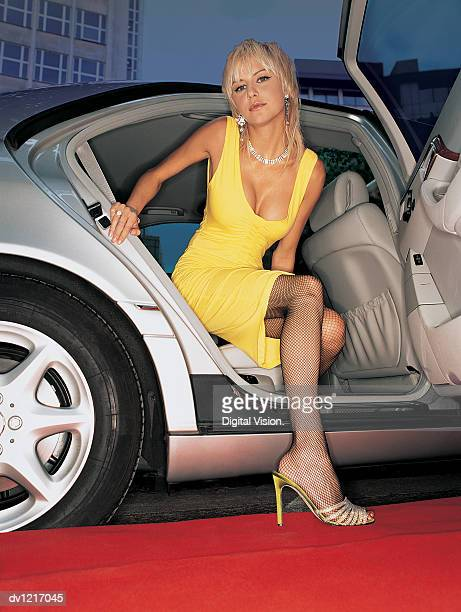 Young Woman in an Evening Gown Getting Out Of the Back Seat of a Car Onto a Red Carpet