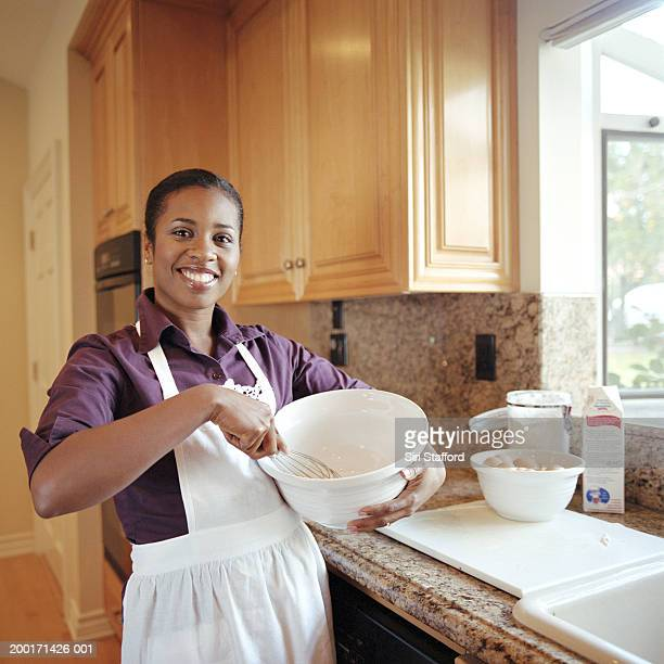 Young woman in apron holding mixing bowl