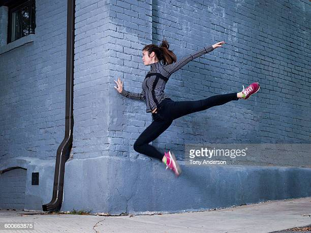 Young woman in athletic wear jumping near wall