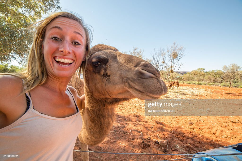 Young woman in Australia takes selfie portrait with camel : Stock Photo