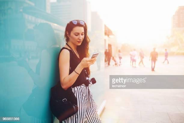 バンコクのダウンタウン地区、彼女の携帯電話にテキスト メッセージの若い女性 - 若い女性一人 ストックフォトと画像