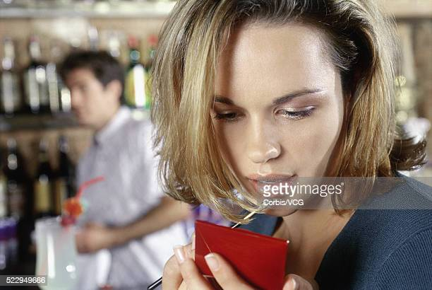 Young Woman in Bar Applying Lip Gloss