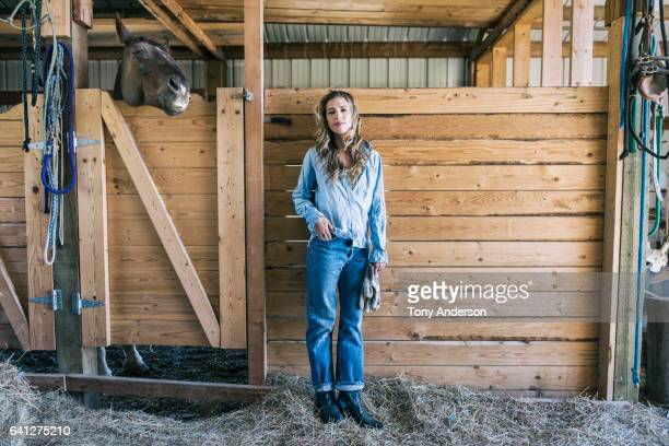 Young woman in barn with her horse
