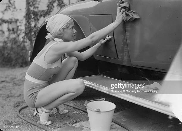 Young woman in bathing costume cleans car Photograph taken by Zoltan Glass c1930 Photograph taken for advertisement series in the early 1930's by...
