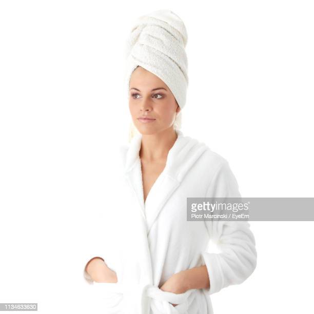 young woman in bathrobe and towel on head against white background - バスローブ ストックフォトと画像