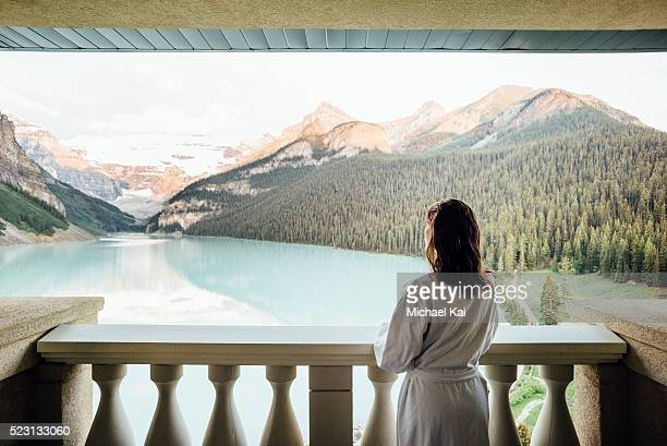 Young woman in bathrobe overlooking Lake Louise from balcony, Banff National Park, Alberta, Canada