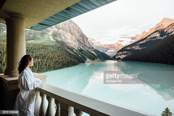 Young woman in bathrobe overlooking Lake Louise from balcony
