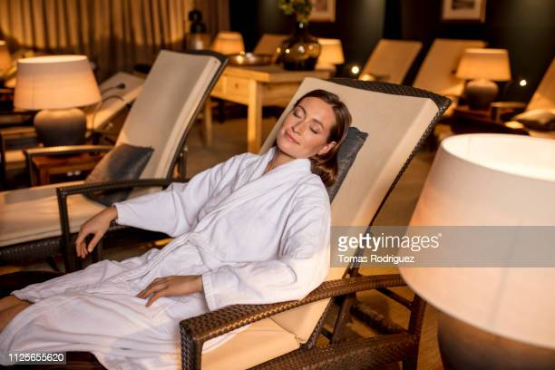 young woman in bathrobe resting in lounge chair in relaxation room of a spa - health farm - fotografias e filmes do acervo