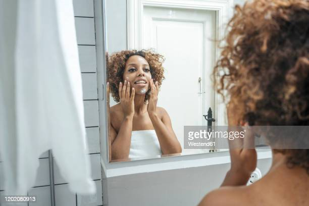 young woman in bathroom applying face cream - applying stock pictures, royalty-free photos & images