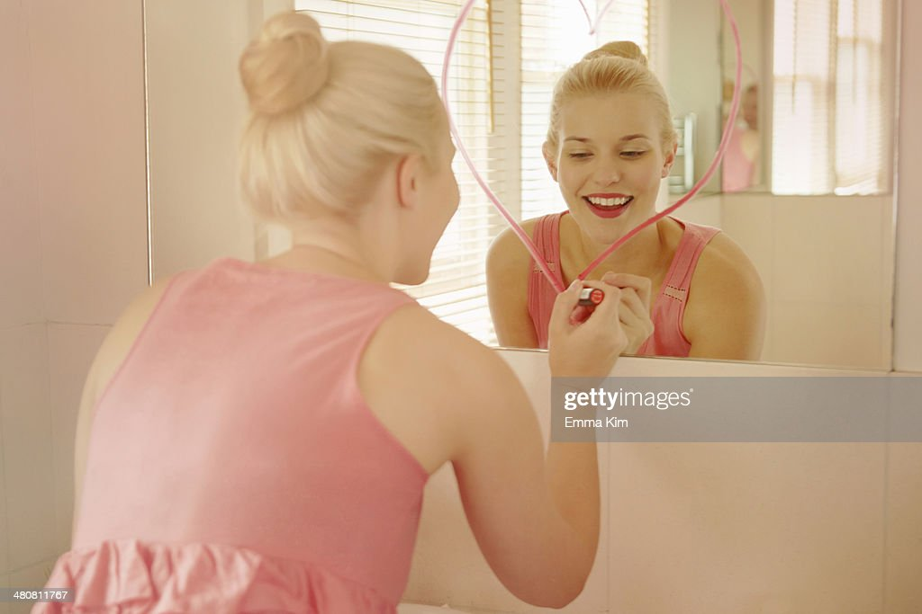 Young woman in bathroom drawing heart shape on mirror with lipstick : ストックフォト