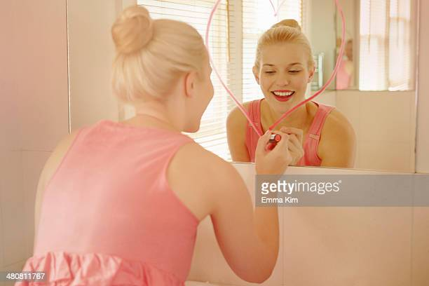 Young woman in bathroom drawing heart shape on mirror with lipstick