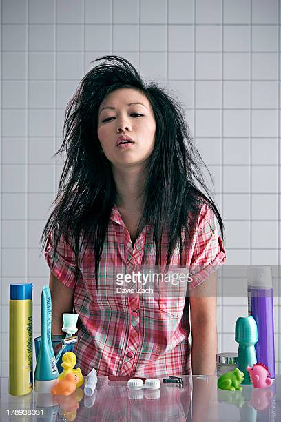 Young woman in bathroom looking tired