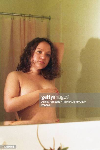 young woman in bathroom mirror - 67percentcollection stockfoto's en -beelden