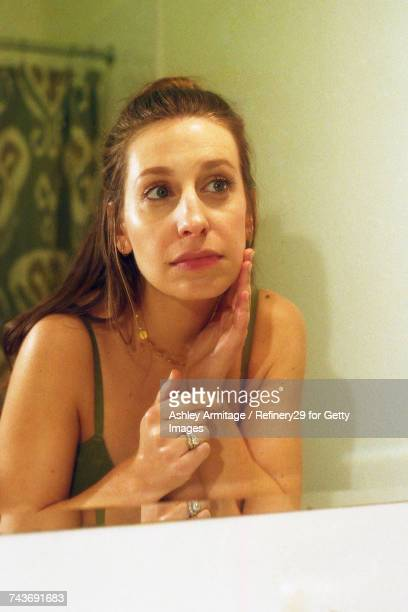 young woman in bathroom mirror - 67percentcollection stock pictures, royalty-free photos & images
