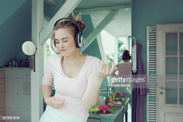 Young woman in bathroom with headphones playing air guitar
