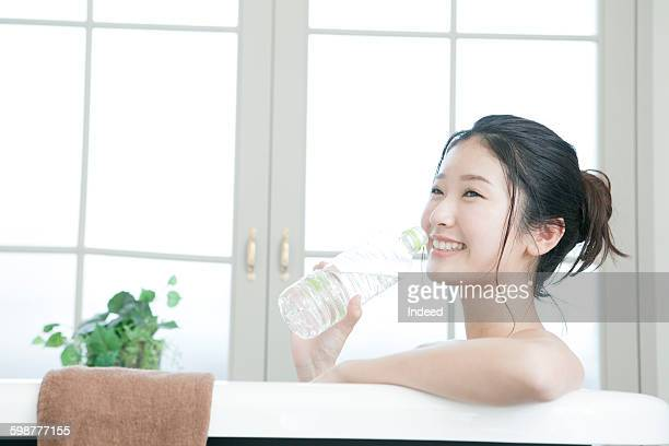 Young woman in bathtub drinking water