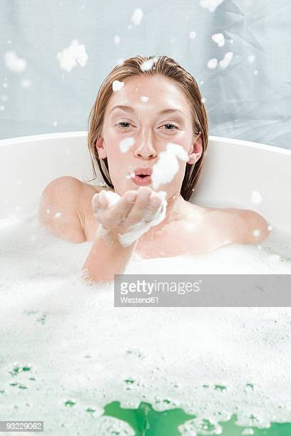 Young woman in bathtub, fooling about
