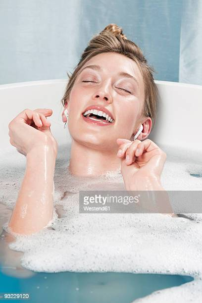Young woman in bathtub listening to music, eyes closed, smiling
