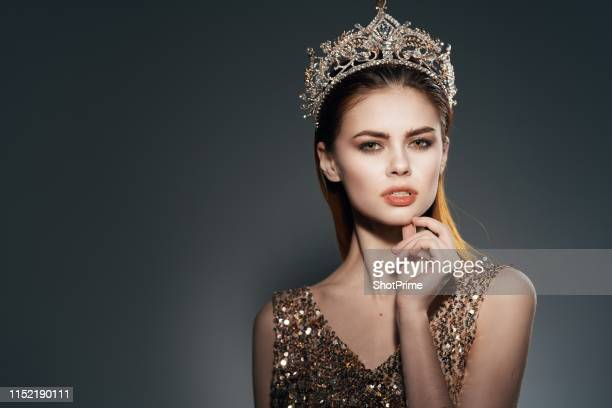 young woman in beautiful crown is looking at the camera - princess stock pictures, royalty-free photos & images