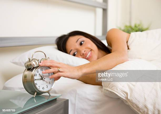 Young woman in bed adjusting alarm