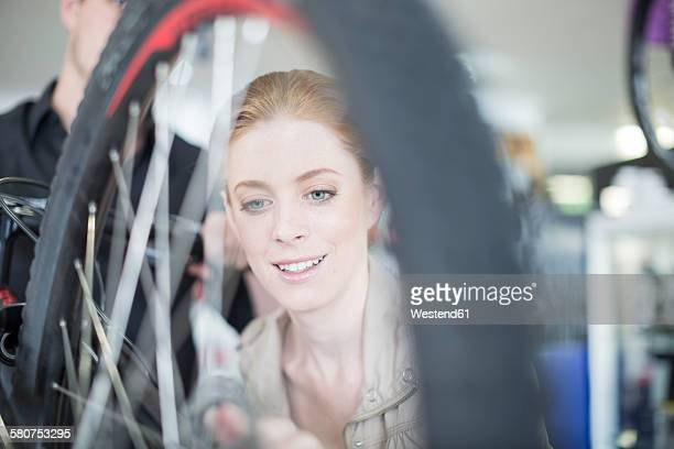 Young woman in bicycle shop looking for bike