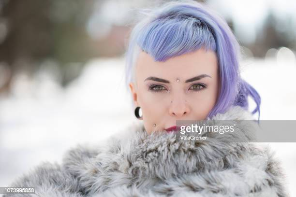 young woman in big fake fur coat outdoors in winter. - purple hair stock photos and pictures
